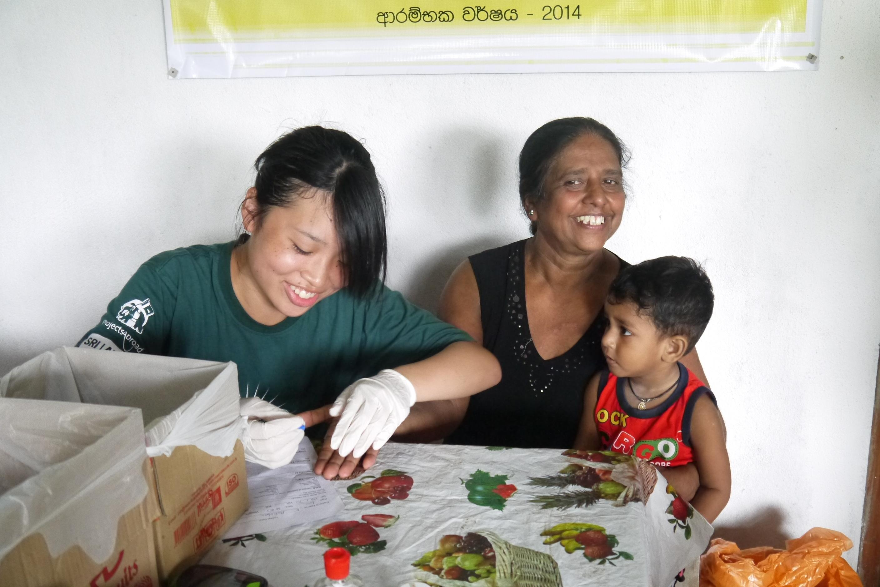 A female health care student is seen taking blood pressure and sugar levels ina . local surgery as part of her nursing internship in Sri Lanka with Projects Abroad.